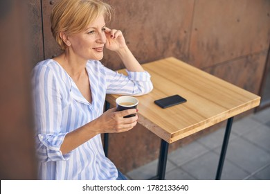 Pensive beautiful mature blonde Caucasian woman with a cup of coffee looking into the distance