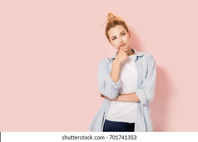 Pensive beautiful woman on pink background with copy space
