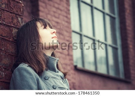 pensive beautiful young girl standing near a brick wall and looking up