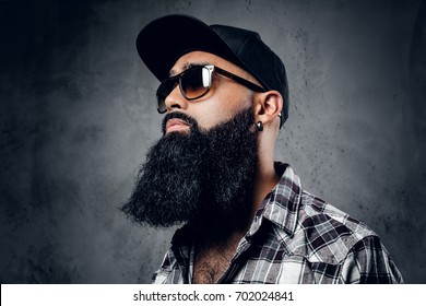 Pensive Black bearded male dressed in a fleece shirt, sunglasses and baseball cap posing over grey background.