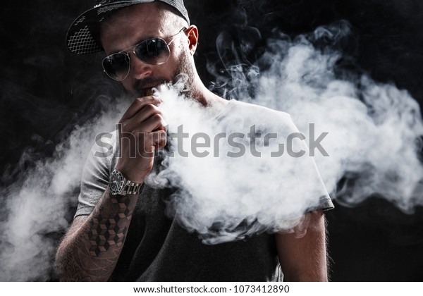 Pensive Black bearded male dressed in a grey shirt, sunglasses and baseball cap vaping. man in holding a mod. A cloud of vapor. Black background.
