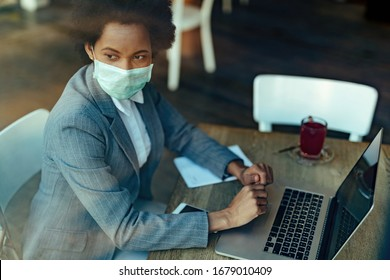 Pensive black businesswoman using laptop while sitting in a cafe with protective mask on her face.