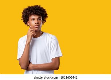 Pensive schwarze Teenager. Entscheide dich! Verwirrter junger afrikanischer Kerl einzeln auf orangefarbenem Kopienraum. Erstellen Sie Ideen. Soziale Toleranz. Werbehintergrund