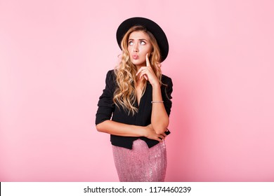 Pensive blonde woman in black hat posing over pink background. Wearing trendy dress with sequence , black jacket and hat.