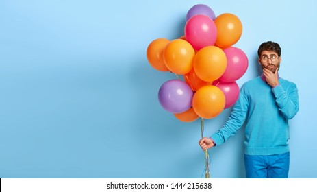 Pensive boss looks thougthfully aside, touches chin, thinks about anniversary of founding own company, holds bunch of helium balloons, celebrates jubilee, isolated on blue wall, copy space area