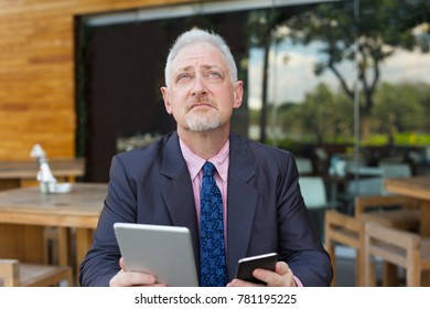 Pensive Boss Using Tablet and Smartphone Outdoors