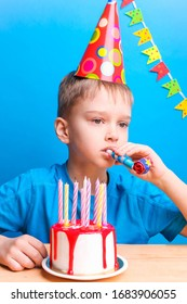 A pensive boy in a festive cap is holding a pipe on a blue background. White cake with red icing and puffed candles. Birthday concept.