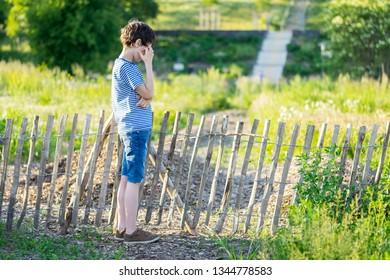 A pensive boy next to a crooked wooden fence.
