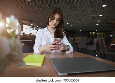 Pensive brunette business woman in trendy outfit reading electronic book via modern smart phone analyzing information while sitting in coffe shop