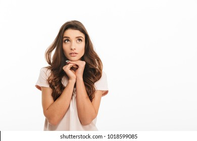 Pensive brunette woman in t-shirt reclines on her arms and looking up over white background