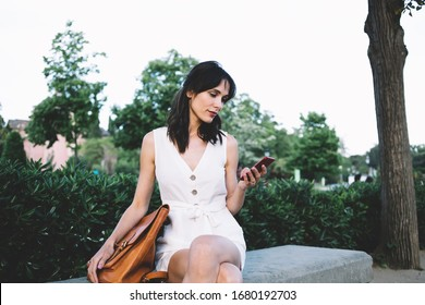 Pensive brunette woman in white dress and elegant bag surfing mobile phone sitting on bench in street with green fence