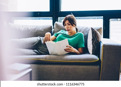 Pensive brunette young woman lying on comfortable sofa and read interesting literature plot of book enjoying leisure time and relaxing in modern apartment.hipster girl with bestseller resting on coach