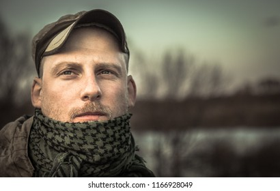 Pensive brutal thoughtful man soldier looking into the distance grunge portrait