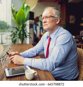 Pensive Business Man Using Smartphone in Cafe