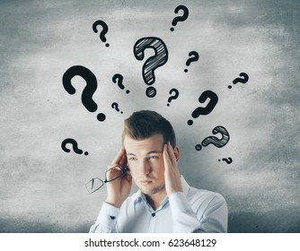 Pensive businessman with drawn question marks. FAQ concept