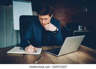 Pensive businessman in formal wear concentrated on solution for project writing plan in notepad at desktop,confident economist making accountings for statement at working place with laptop computer