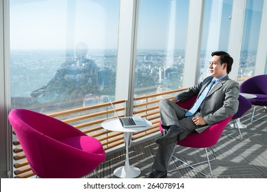 Pensive businessman looking at the city through the office window