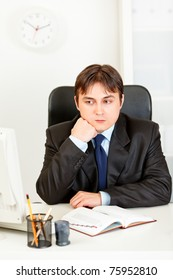 Pensive businessman man sitting at office desk and keep head on hand