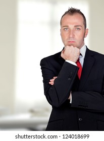Pensive businessman in the office witha a bright background