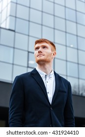 Pensive businessman standing outdoors with glass building on background