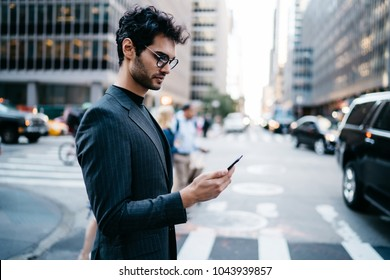 Pensive businessman in suit read incoming notification with money balance on account received on smartphone crossing New York street.Prosperous entrepreneur in formal wear checking mail on telephone
