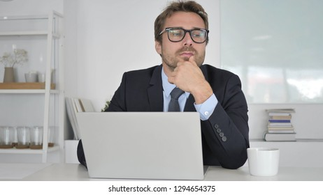 Pensive Businessman Thinking and Working on Laptop