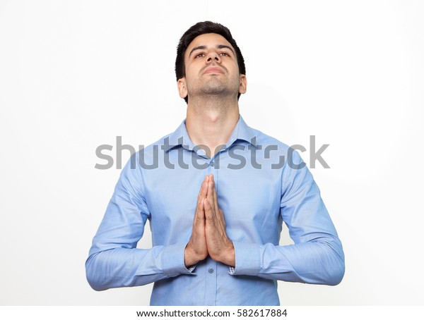 Pensive businessman with touched palm praying