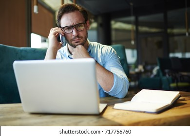 Pensive businessman in trendy spectacles having serious phone conversation with colleague while solving problem with report online.Thoughtful boss concentrated on checking accountings on laptop