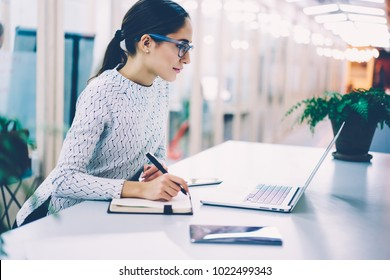 Pensive businesswoman reading information browsed on laptop computer making notes planning startup,female manager organizing working process in office creating scedulevia application on netbook