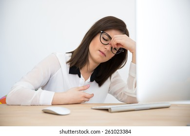 Pensive businesswoman sitting at the table with closed eyes