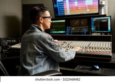 Pensive busy hipster young woman in denim jacket working on professional analog mixing console while creating unique soundtrack in recording studio