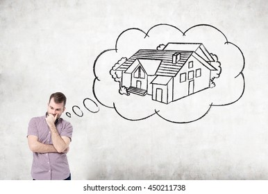 Pensive casual young man daydreaming about buying a house on concrete background. Concept of mortgage and real estate