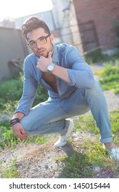 pensive casual young man posing outdoor in a crouched position with his hand at his chin, looking at the camera