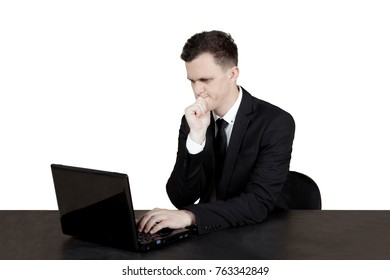 Pensive Caucasian businessman working with a laptop computer while thinking idea, isolated on white background