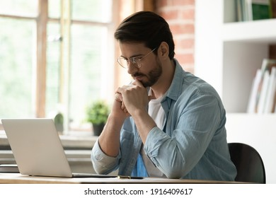 Pensive Caucasian male employee look at laptop screen work on gadget thinking pondering. Thoughtful man worker use computer consult client online, analyze report or solve business problem in office.