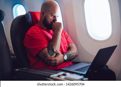 Pensive caucasian man aircraft passenger sitting with laptop next to airplane window in business class cabin, Male freelancer work during flight connecting to wireless internet on board via computer