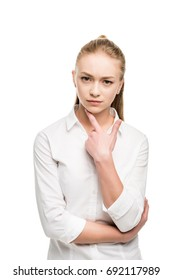 pensive caucasian teenage girl with finger on chin looking at camera isolated on white