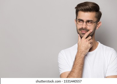Pensive caucasian young man in glasses wear white t-shirt isolated on grey studio background peek at blank copy space thinking, thoughtful male in spectacles look at offer deal considering option