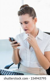 Pensive classy businesswoman looking at her smartphone in bright office