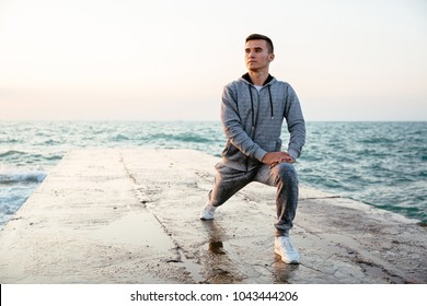 Pensive concentrated man in sportswear doing lunges, stretching, while having workout on pier, near the sea. Outdoors.