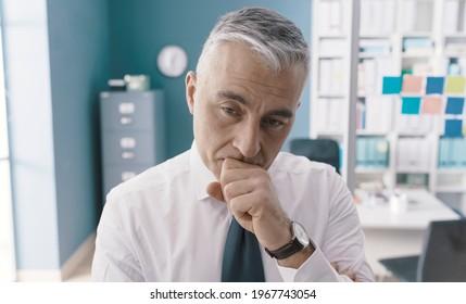 Pensive betroffene Geschäftsleute, die in seinem Büro stehen und denken: Geschäftslösungen und Strategiekonzept