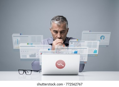 Pensive confident businessman reading financial reports on visual screens and working with a laptop, finance and technology concept