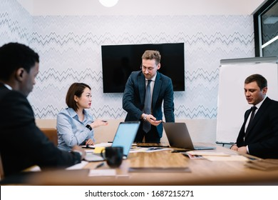 Pensive confident multiethnic adult business partners in elegant clothes developing strategy while working at table with papers and laptops during meeting in conference room