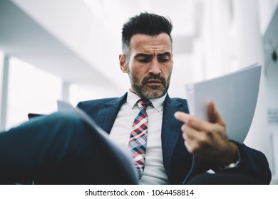 Pensive confident proud ceo dressed in formal wear checking paper financial documents sitting in office.Concentrated entrepreneur in stylish suit reading information data in accounting reports