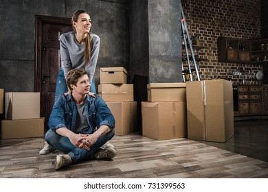 pensive couple looking away in room with cardboard boxes at new home