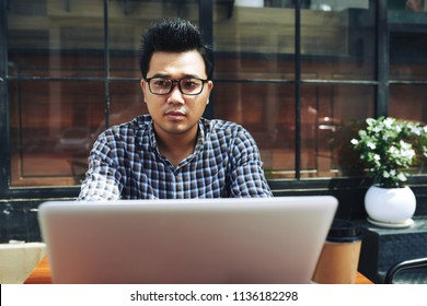 Pensive creative freelancer working on laptop at table in cafe