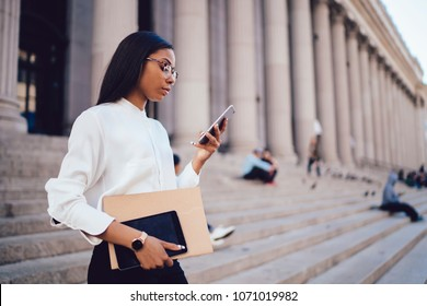 Pensive dark skinned student of faculty of law checking mail and reading notification with financial news on smartphone device connected to smartphone standing outdoors near university building