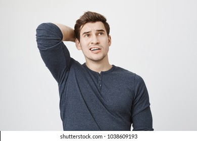 Pensive dark-haired man in long-sleeved t-shirt posing against gray background, frowns face, looks thoughtfully upwards, scratches back of head. Male trying to remember what he forgot.