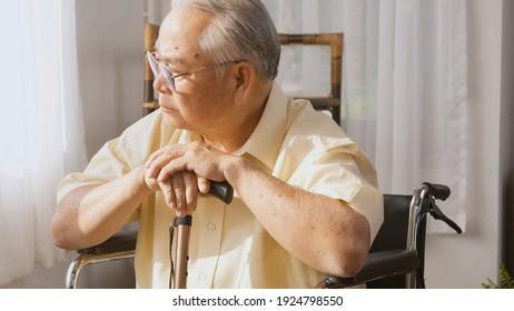 Rentner behinderter älterer Patienten sitzen allein auf Rollstuhl, Trauriger und depressiver, einsamer älterer Mann aus Asien fühlen sich einsam und langweilig und warten auf die Pflege der weißen Raum-Demenz und Alzheimer