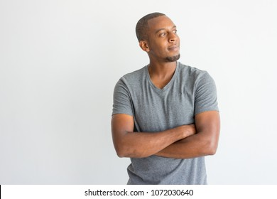 Pensive dreamy young African man with crossed arms looking away. Introspective handsome guy in t-shirt thinking. Inspiration concept